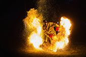 A Stunning Fire Show Against A Dark Night. A Man In A Chemical Fire Protection Suit And A Gas Mask P poster