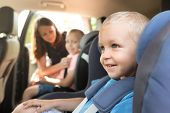 Boys Buckled Into Car Seat. Mother Takes Care About Her Children In A Car. Safe Family Travel Concep poster