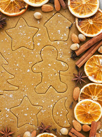 stock photo of gingerbread man  - Christmas baking background dough cookie cutters spices and nuts - JPG