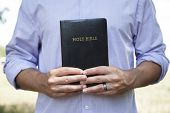 Man Holding Black Bible