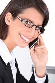 Smiling woman wearing trendy glasses and talking on a mobile phone