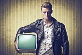 Young man in vintage clothes holding an old television under his arm