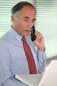 mature businessman on the phone looks stunned
