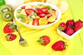 Useful fruit salad of fresh fruits and berries in bowl on tablecloth close-up