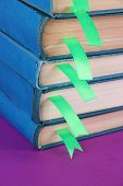 Many books with bookmarks on purple background close-up