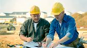 pic of erection  - Construction workers look at and discuss plans - JPG