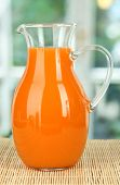 Orange juice in pitcher on table in room