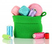 Colorful yarn for knitting in green basket isolated on white