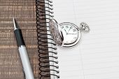 Pocket Watch And Pen On The Notebook Into A Cell. In The Office.