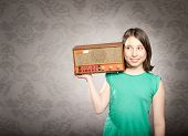 young woman holding old retro radio