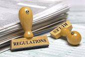 stock photo of policy  - rubber stamps marked with regulations and rules - JPG