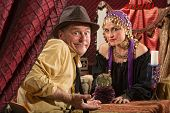 stock photo of gullible  - Fortune teller in head scarf with skeptical customer and crystal ball - JPG