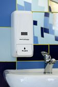 stock photo of wash-basin  - Soap dispenser above the sink or basin in blue tile bathroom - JPG
