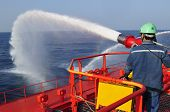 stock photo of fire extinguishers  - Fireman testing a fire fighting water gun onboard of tanker ship - JPG