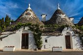picture of conic  - Trulli houses with painted symbols on the conical roofs in Alberobello Italy Puglia - JPG