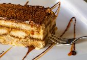 stock photo of cream cake  - a huge chunk of the traditional Italian unforgettably delicious rich and sweet tiramisu cake with cinnamon caramel honey and dessert fork - JPG