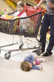 stock photo of spoiled brat  - young family shopping with trolley at supermarket - JPG