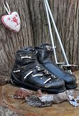stock photo of ski boots  - old ski boots in a rustic setting with a heart shaped cushion - JPG