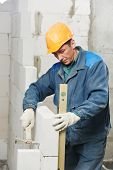 construction mason worker bricklayer inspecting with level installation of calcium silicate brick du