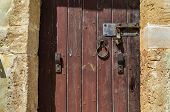 Old Wooden Door With Rusty Locks, Latches And Handles