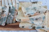 Mouldy bread on cutting board, on wooden background