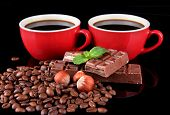 Red cups of strong coffee with coffee beans and chocolate bars close up