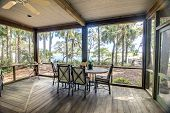 rustic screen porch with forest and waterfront view
