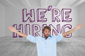 image of raised-eyebrow  - Handsome man raising arms in front of were hiring graphic in a grey room - JPG