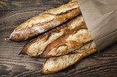 image of baguette  - Four baguette bread loaves in paper bag on wooden background - JPG