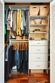 stock photo of wardrobe  - Clothes hung neatly in organized closet at home - JPG