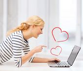 love and internet concept - smiling student girl pointing her finger at laptop screen in college