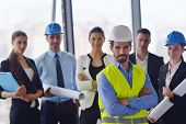 image of blueprints  - business people group on meeting and presentation  in bright modern office with construction engineer architect and worker looking building model and blueprint  plans - JPG