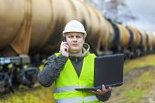 Railroad employee with phone and PC near tank wagons