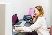 Smiling Woman On Telephone At Office Desk