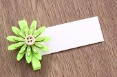Green Artificial Flowers And Note Paper Stuck On Dark Wood.
