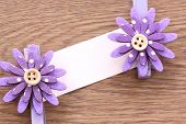 Purple Artificial Flowers And Note Paper Stuck On Dark Wood.