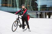 Portrait of young female cyclist in protective gear with courier delivery bag