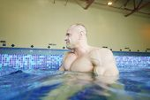 Wet bodybuilder looks away in pure water of swimming pool of gym hall