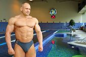 Bodybuilder in swimming trunks stands near indoor pool of gym hall