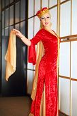 Young woman in red Andalusian costume stands in graceful pose