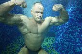 Bodybuilder in swimming trunks sits on bottom of pool underwater among many bubbles
