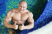 Top view of happy bodybuilder showing thumbs-up gesture in swimming pool