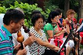 Beijing, China - Jul 17, 2011: Women And Men Are Playing On Traditional Flutes In Jingshan Park. It'