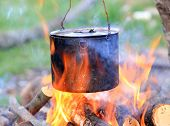 tourist kettle among hot flame of campfire