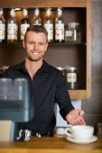 Portrait of smart young bartender gesturing at counter in cafe