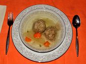 stock photo of matzah  - Matzo ball soup on an orange table cloth - JPG