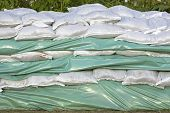 stock photo of tarp  - Wall of sandbags and tarp for flood protection - JPG