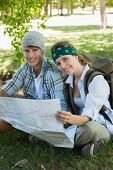 Active smiling couple sitting down on a hike holding map on a sunny day