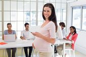 Pregnant office worker touches bump and texts on phone and smiles at camera in the office