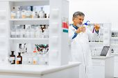 picture of scientific research  - Senior male researcher carrying out scientific research in a lab  - JPG